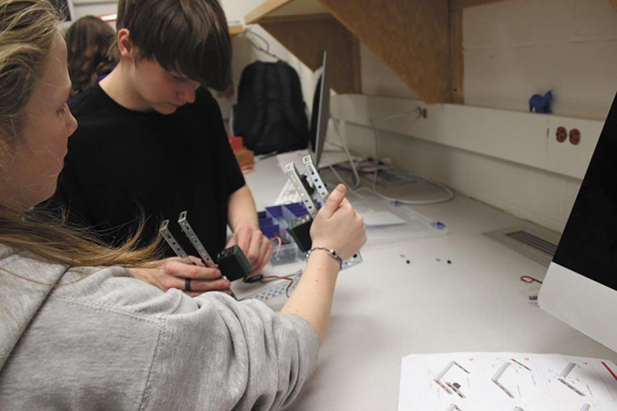 """Clink! While at a meeting for Robotics Club freshman Fianna Glenn and Robert Raffety prepare their robot for competition.""""The hardest part is planning, after that you have to assemble and program which takes one to two months."""""""