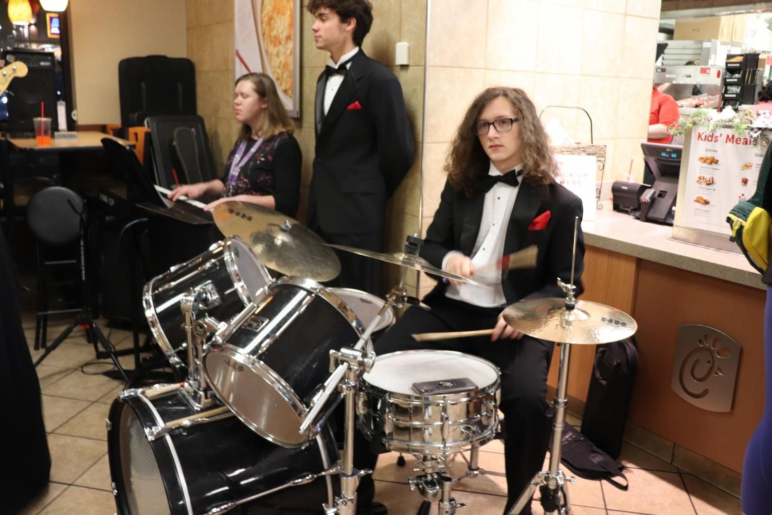 """Junior Christpher Moore plays the drumset. """"Chick-Fil-A night is a fun experience that helps the choir out a lot,it is also a huge fundraiser for us,"""" Moore said. Photo by Cora Bennett"""