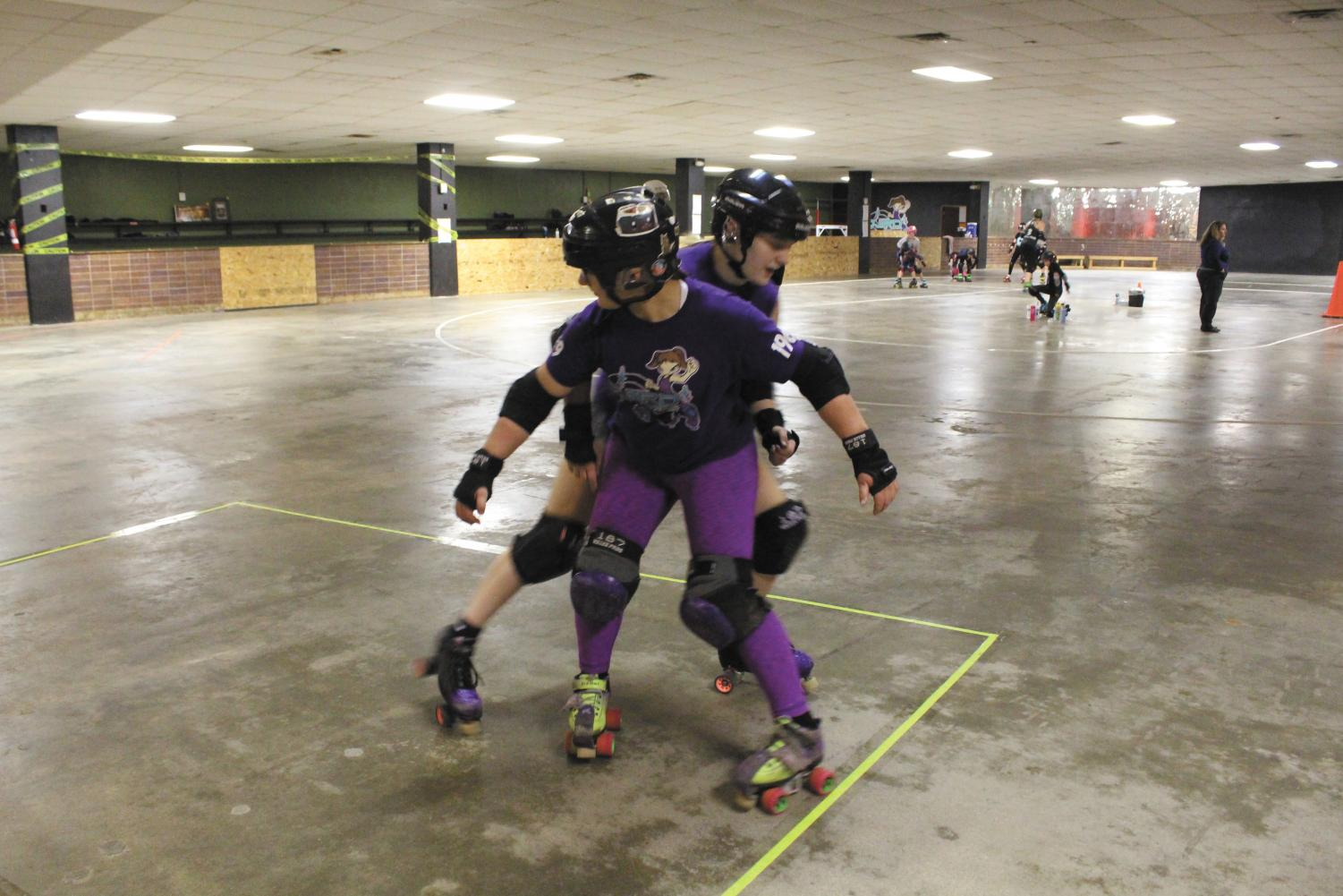"""Freshman Caroline Boucher blocks senior Trinity Hettinger from trying to get around her and score a point. """"I've always loved skating and thought it looked like a great way to take my anger out,"""" Hettinger said. Photo by McKenzie Gandy."""