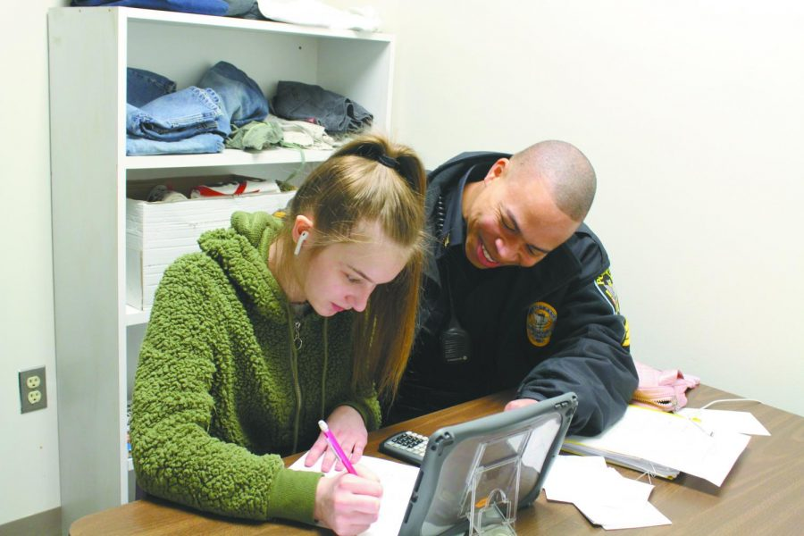 Sgt. Howard Bank assists sophomore Meadoe Anderson with her homework assignment. Banks became the new SRO at East after Officer Anthony Orsi left, and the position gives him many opportunities to interact and build relationships with students.